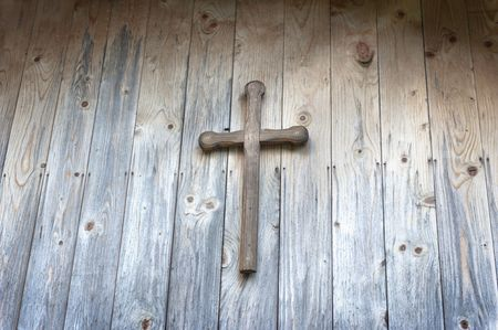 Wooden cross on a wooden wall with a lignt beam accross it