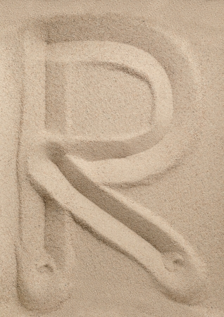 Letter R of the alphabet writing on the sand