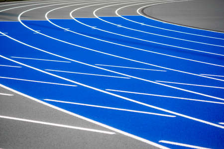 Foto de Curved blue and gray running track with textured surface, crisp lines - Imagen libre de derechos
