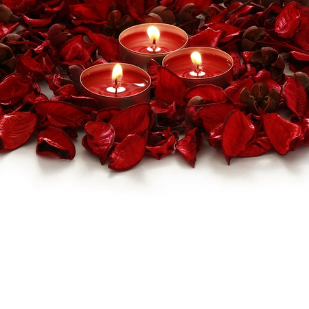 Foto de red roses and candles on whiter background with space for your text - Imagen libre de derechos
