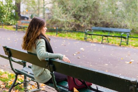 Photo for Beautiful girl sitting on a bench, sunny autumn day in the park, relaxing, after work business woman - Royalty Free Image