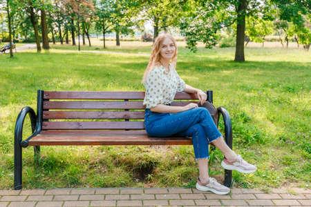 Photo pour The beautiful young woman sits on a bench - image libre de droit