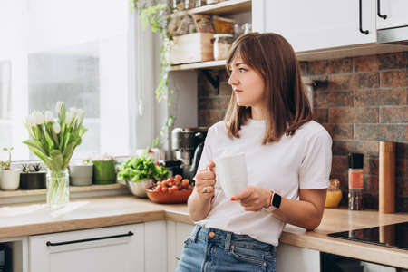 Photo for Close up woman in white t-shirt drinking coffee or tea in kitchen at home. Early breakfast in the morning, rest time - Royalty Free Image