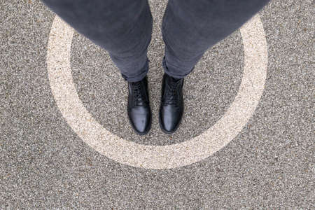 Photo for Black shoes standing in white circle on the asphalt concrete floor. Comfort zone or frame concept. Feet standing inside protected area zone circle. Place for text, banner - Royalty Free Image