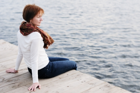 A woman is sittng on wood boards by the water