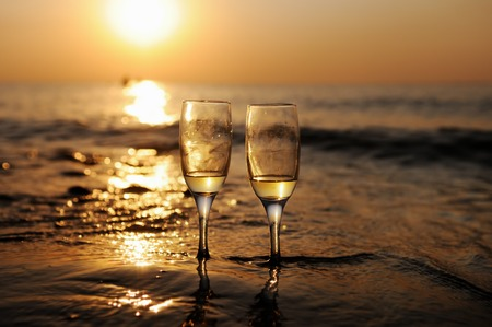 Photo pour Romantic beach evening on the sunset with two glasses of white wine - image libre de droit