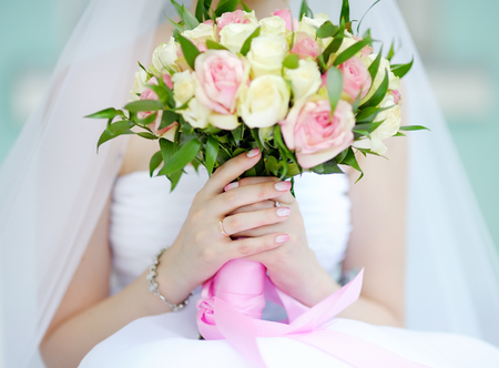 Photo pour Bride holding wedding flowers roses bouquet, focus in hand and wedding ring - image libre de droit