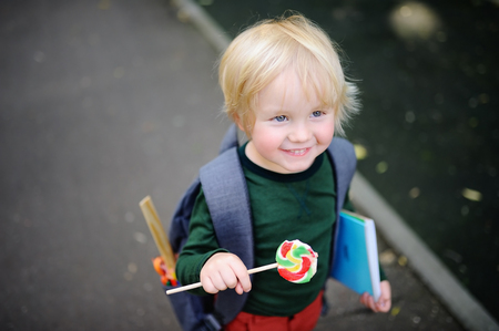 Cute little schoolboy outdoors on sunny autumn day. Young student with his backpack and lollipop. Education for small kids. Back to school concept.