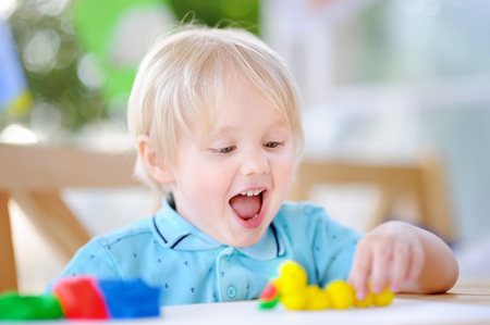 Photo for Creative boy playing with colorful modeling clay at kindergarten. Little kid molding at home. Development toys for preschooler children - Royalty Free Image