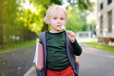 Cute little schoolboy outdoors with his backpack and lollipop.