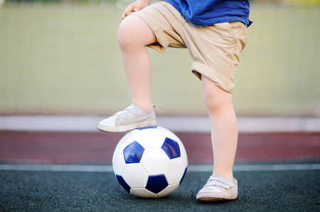 Foto de Little boy having fun playing a soccer/football game on summer day. Active outdoors game/sport for children. Kids soccer classes and camps - Imagen libre de derechos