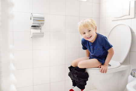 Foto de Cute little boy in restroom. Toddler child trainig use toilet. Hygiene for little child - Imagen libre de derechos