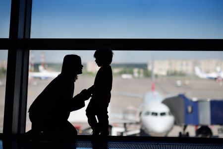 Young woman with little boy having fun at the international airport. Mother with her cute little son waiting boarding. Family travel or immigration concept
