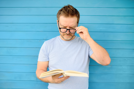 Photo pour Portrait of mature man with big black eye glasses trying to read book but having difficulties seeing text because of vision problems. Problems disorder vision. - image libre de droit