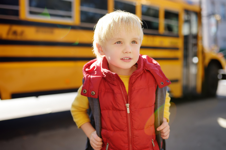 Foto de Pupil with schoolbag with yellow school bus on background. Back to school. - Imagen libre de derechos