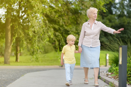 Photo pour Beautiful granny and her little grandchild walking together in park. Grandma and grandson - image libre de droit