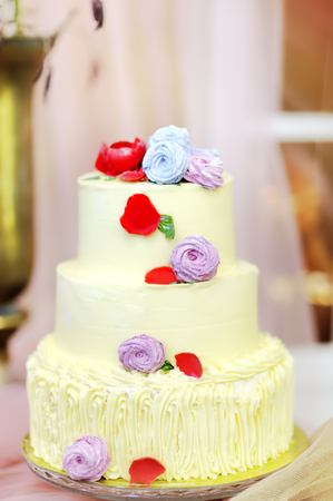 Photo pour Traditional anniversary/wedding multi-layer cake. Beautiful delicious sweet dessert decorated with flowers on blurred background - image libre de droit
