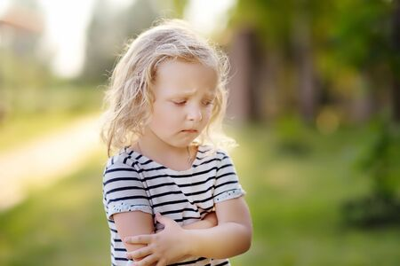 Photo for Upset or offended little girl standing on street of small town's or village's. ?risis of three years. Escape from the house. - Royalty Free Image
