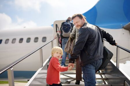 Little boy and his father climb the gangway into the plane against the background of people. Back view. Travel for family with little kids.