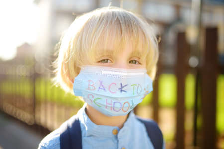 Photo for Child in face mask going at reopen school after covid-19 quarantine and lockdown. It is new normal for protection and prevention while outbreak of coronavirus or flu. Kids back to school concept. - Royalty Free Image