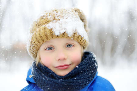 Photo pour Portrait of funny little boy in blue winter clothes walks during a snowfall. Outdoors winter activities for kids. Cute child wearing a warm hat look at you - image libre de droit