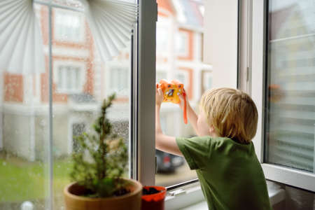 Photo pour Little boy watching the rain outside at opened window and taking photo. Bad weather - wind and downpour. Child boring and waiting of rainfall finish. Inquisitive kid explore nature. - image libre de droit
