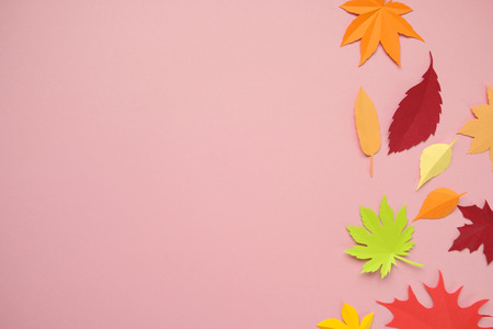 Leaves of paper fall red, orange, yellow leaf fall. Pink background. Handmade origami.の写真素材