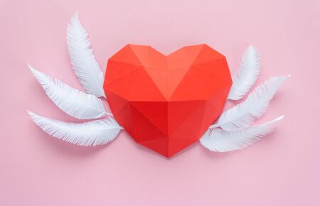 Paper hearth with shadow. Red polygonal paper heart with white feather for Valentine's day or any other Love invitation cards.