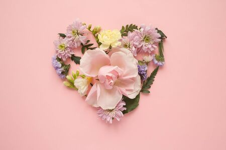 Photo pour Heart made of different flowers on pink background. Flat lay. Love concept. - image libre de droit