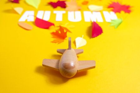 Photo pour wooden toy airplane carries lettering autumn with leaves of paper fall red, orange, yellow leaf fall. Yellow background. Handmade origami. - image libre de droit