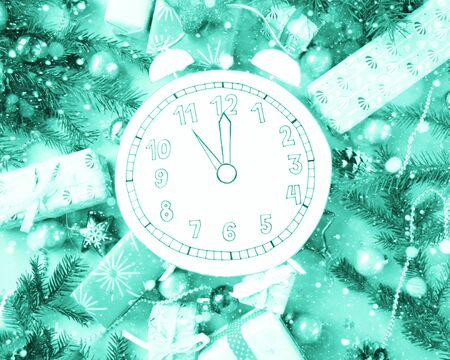 Foto de Merry Christmas and happy new year. Clock, cut out of paper, surrounded by fir-tree branches and gifts on blue background - Imagen libre de derechos