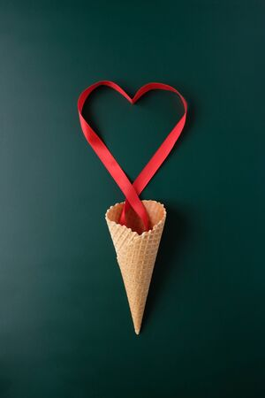 Foto de Waffle cone with valentine elements on dark background. Valentine's day concept. Red ribbon in the shape of heart. Valentine's day - Imagen libre de derechos