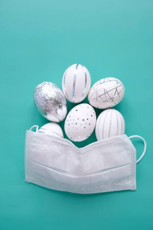 Photo for Easter time in quarantine concept. Face mask on easter eggs on the table on a white background. Concept of Easter holyday and spring break - Royalty Free Image