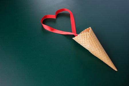 Foto de Waffle cone with red ribbon in the shape of heart - Imagen libre de derechos