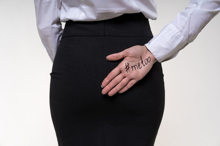 Foto de Assistant girl hides behind her hand a hand with an inscription me too. Sexual harassment and abuse at work concept. Physical fight at workplace. - Imagen libre de derechos