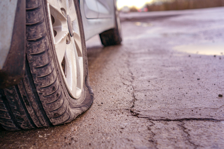 Photo pour Flat tyre on road. Car tire leak because of nail pounding. Toned - image libre de droit