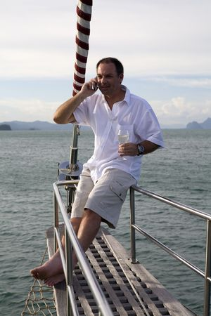 Handsome man on deck of yacht with mobile phone and drinking wine