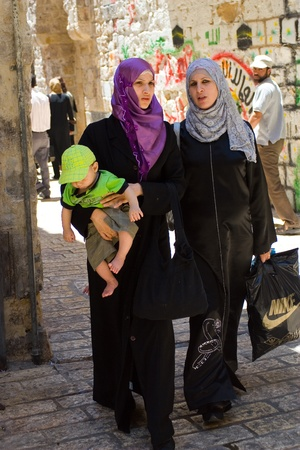 Old City, Jerusalem, Israel - July 17, 2009: Two Arab Women walking on traditional costume, one holding baby.