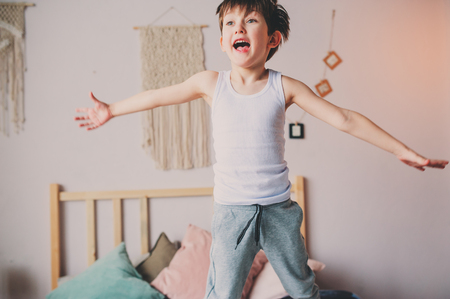 Photo pour happy naughty boy jumping in bed in early morning. Hyperactive kids, casual lifestyles. - image libre de droit
