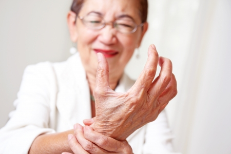 Elderly woman with hand arthritis grimace in pain.