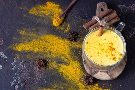 Photo pour Golden milk or latte with turmeric (curcuma) powder with spices, dark brown concrete background. Trendy detox, immune boosting, anti-inflammatory healthy cozy drink. - image libre de droit