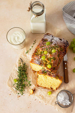 Foto für Delicious homemade grape loaf cake with thyme and sugar powder on parchment paper. Light stone background. - Lizenzfreies Bild
