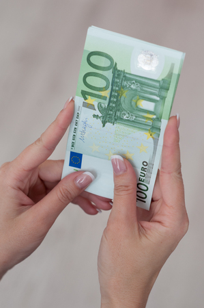 Famale hand holding several euro money banknotes.