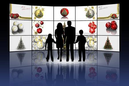 Foto per Natale. Famiglia di fronte a schermi con decorazioni natalizie. - Immagine Royalty Free