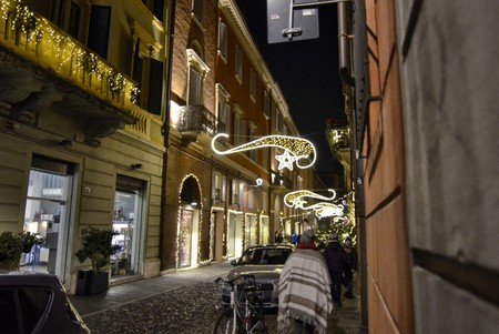Foto per Modena, Emilia Romagna, Italy. December 2018. Night view of the streets of the historic center. The Christmas atmosphere is underlined by the bright decorations. People stroll enjoying the place. - Immagine Royalty Free