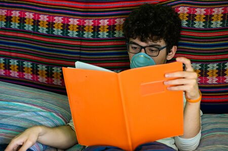 A bedridden Caucasian boy wears a blue protective mask. He is studying his orange-covered notebook. Home study concept during coronavirus pandemic quarantine.