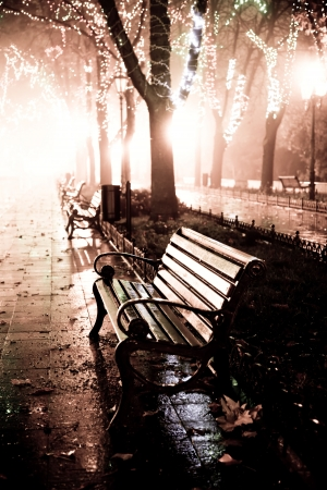 Bench in night alley with lights in Odessa, Ukraine. Photo in retro style.