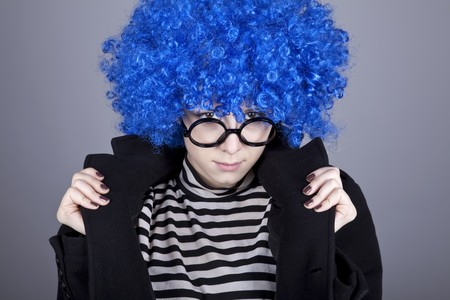 Funny fashion blue-hair girl in glasses and black coat. Studio shot.の写真素材