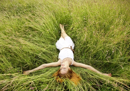Beautiful girl lying down at grass.