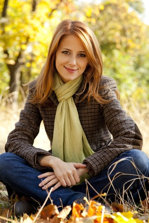 Portrait of red-haired girl in the autumn park. Outdoor shot.
